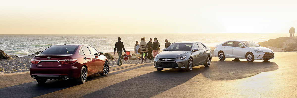 Three Toyota Camrys parked beside a beach
