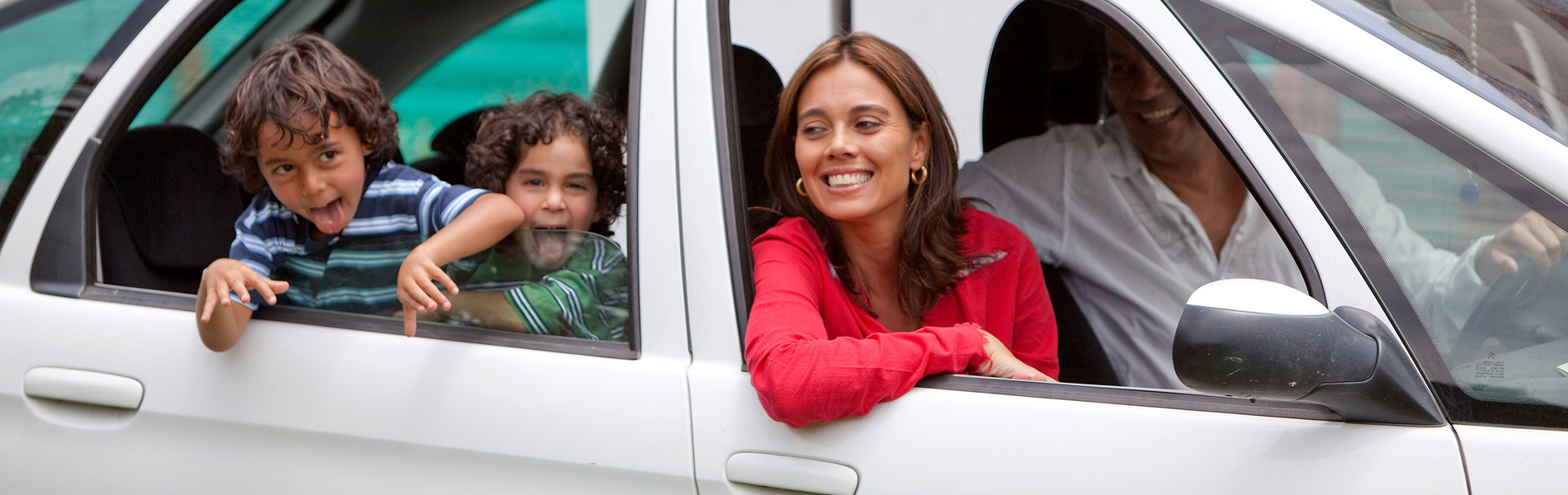 Couple with kids smiling in a car