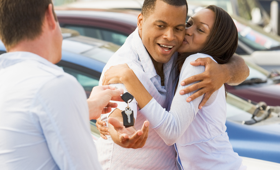 Couple embracing each other as they are being given keys to car by salesperson