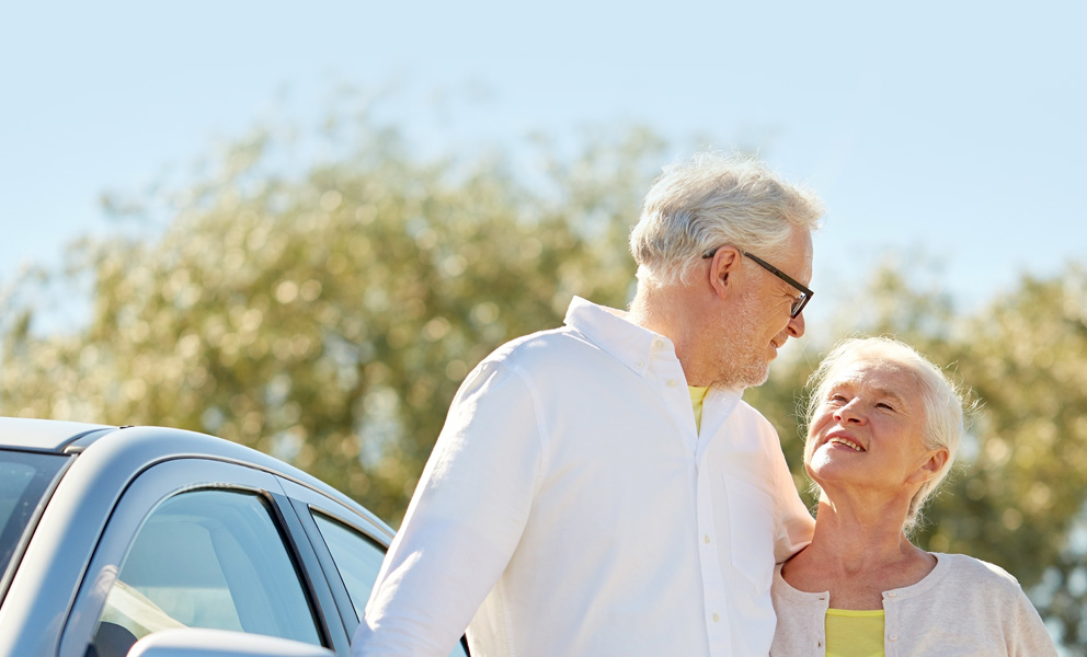Older couple smiling at each other in front of a car